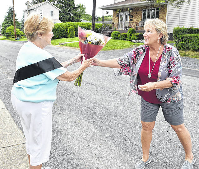 <p>Nancy (Gillespie) Stewart hands her mother, Joan Pribula, a bouquet of flowers on her 90th birthday on June 4. Stewart traveled from Krum, Texas, to celebrate her mother's birthday.</p> <p>Tony Callaio   For Sunday Dispatch</p>