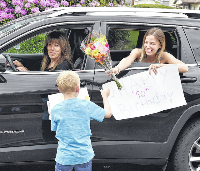 <p>Quinn Gillespie, granddaughter of Joan Pribula, hands her cousin R.J. Bartoli flowers for her grandmother. Driving is Quinn's mother Barbara Parrino Gillespie.</p> <p>Tony Callaio   For Sunday Dispatch</p>