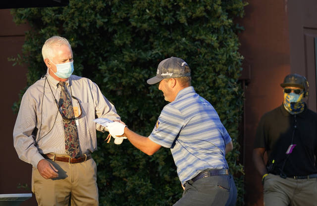 <p>A rules official hands a scorecard to Ryan Palmer at the first tee to open the first round of the Charles Schwab Challenge on Thursday at Colonial.</p> <p>David J. Phillip   AP photo</p>