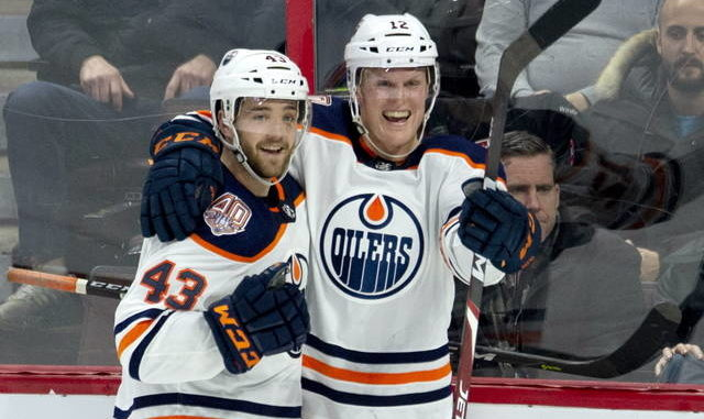"""FILE - This Feb. 28, 2019, file photo shows Edmonton Oilers center Colby Cave (12), right, celebrating his goal with teammate Josh Currie during the third period of an NHL hockey game against the Ottawa Senators in Ottawa, Ontario. Edmonton Oilers prospect Cooper Marody has written a song in memory of teammate Colby Cave to raise money for a memorial fund. Cave, from Battleford, Saskatchewan, died April 11 in a Toronto hospital after suffering a brain bleed. He was 25. Marody's song """"Agape"""" will be released Friday, June 12, 2020, on Apple Music and Spotify. Marody, from Brighton, Michigan, and Cave were teammates last season on the American Hockey League's Bakersfield Condors. (Adrian Wyld/The Canadian Press via AP, File)"""