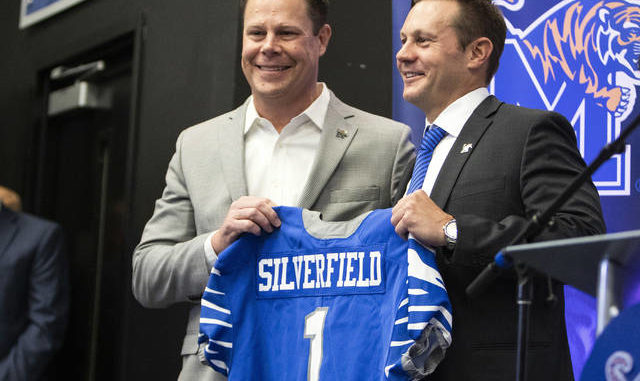 In this Dec. 13, 2019, file photo, Memphis director of athletics Laird Veatch, left, presents Memphis head football coach Ryan Silverfield, right, with a team jersey in Memphis, Tenn. As football players start returning to campus, college officials have a wide range of opinions on whether to let the public know how many of their athletes test positive for coronavirus. Just over half of the 64 Football Bowl Subdivision members that responded to an Associated Press survey said they were still deciding whether to announce the number of student-athletes with positive tests. AP photo