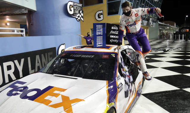 Denny Hamlin jumps from his car after winning a NASCAR Cup Series race Sunday in Homestead, Fla. AP photo