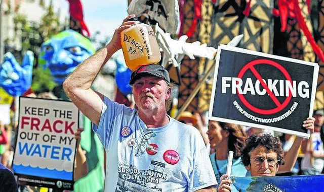 In this Sept. 20, 2012 file photo, Ray Kemble, of Dimock holds a jug of his well water on his head while marching with demonstrators against hydraulic fracturing outside a Marcellus Shale industry conference in Philadelphia. Houston-based Cabot Oil & Gas Corp. was charged Monday following a grand jury investigation that found the company failed to fix faulty gas wells in Dimock and surrounding communities that leaked methane into residential water supplies. AP file photo