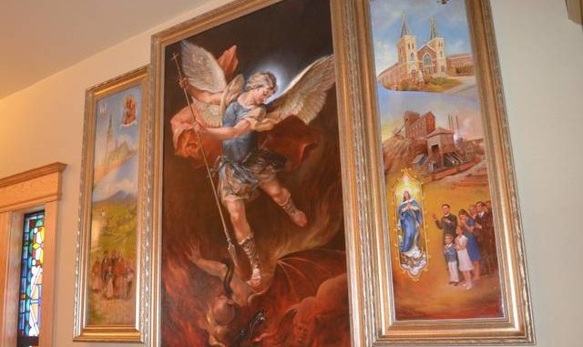 St. Michael the Archangel fights a representation of the devil in the center panel of the new triptych at Sacred Heart of Jesus Church in Dupont. Smaller images in the side panels reflect the history of the parish, which recently celebrated 100 years since the dedication of its current church building on Lackawanna Avenue. Mark Guydish | Times Leader