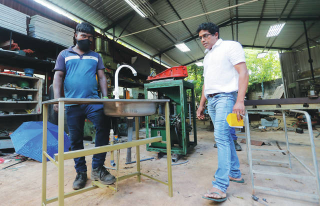 <p>Sri Lankan entrepreneur Nishantha Abeyrathne, right, checks a paddle sink that is made at his workshop in Paththanduwana village in Sri Lanka. Abeyrathne's company seized upon an opportunity when factories in Sri Lanka were allowed to reopen; the government required owners to install sinks so employees could wash their hands, and Abeyrathne designed one with a foot paddle so workers wouldn't have to touch the faucet.</p> <p>AP photo</p>