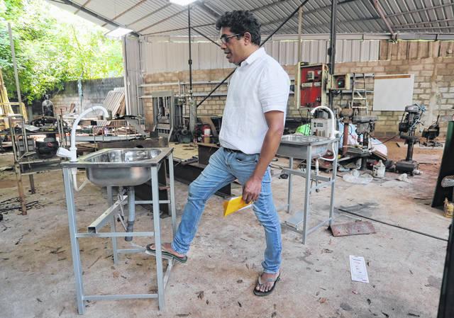 <p>Sri Lankan entrepreneur Nishantha Abeyrathne checks a paddle sink that is made at his workshop in Paththanduwana village in Sri Lanka.</p> <p>AP photo</p>