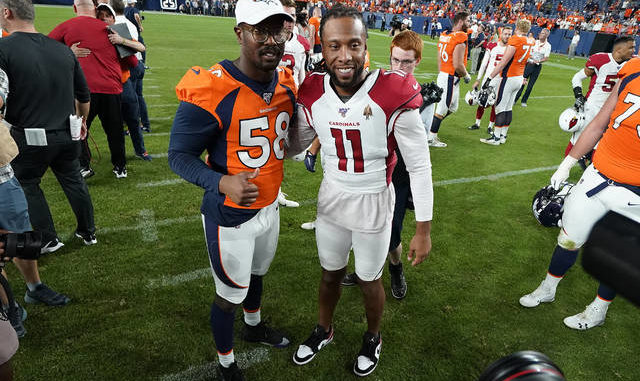 The Broncos' Von Miller, left, and the Cardinals' Larry Fitzgerald meet up after a preseason game last summer. This year's exhibition schedule is set to be cut from four games per team to two because of the coronavirus pandemic. Jack Dempsey | AP file photo