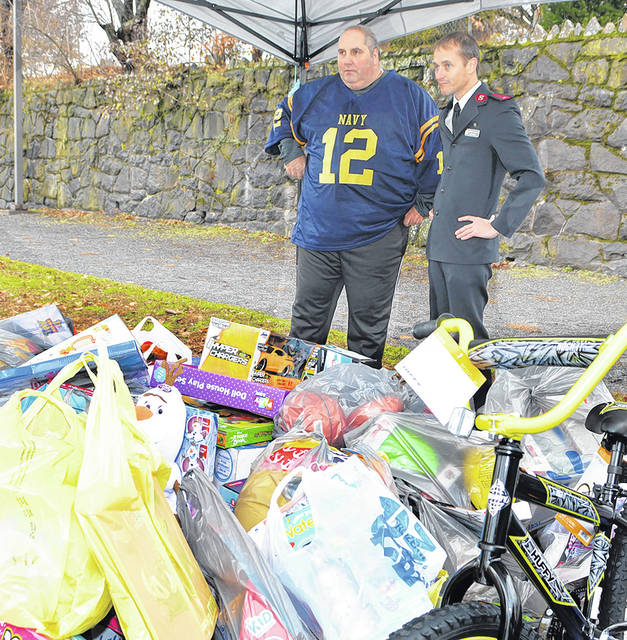 <p>Anthony Marranca, left, Greater Pittston Santa Squad, chats with West Pittston Salvation Army's Lt. Gavin Yeatts in front of more than 150 toys collected to help his Corps branch's Christmas toy drive.</p> <p>Tony Callaio | File photo</p>
