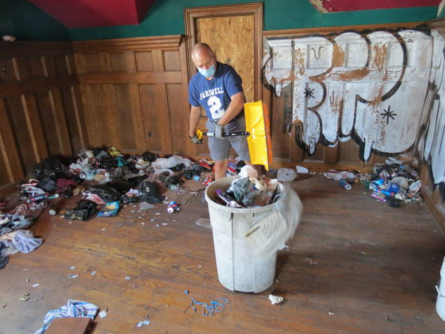 <p>Volunteer Bill Langan of Wilkes-Barre shovels garbage and debris into a container in a second-floor room of the old train station on Saturday morning. About 300 pounds of trash was removed from this room alone in under an hour.</p>