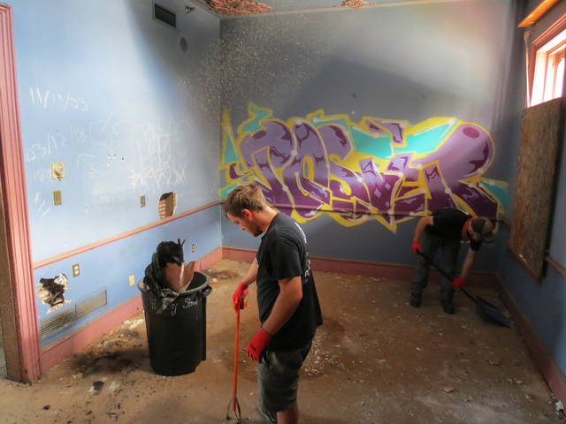 <p>Volunteers Justin Hughes and Damian Bullock shovel up trash in a second-floor room at the former the former Central Railroad of New Jersey train station in Wilkes-Barre on Saturday morning.</p>