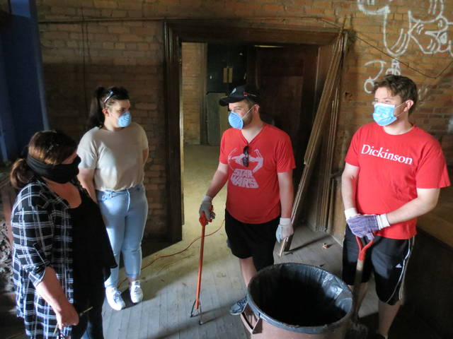 <p>Wilkes-Barre City Councilwoman Beth Gilbert McBride, second from left, talks with Tony Thomas and Mark Shaffer during Saturday's clean-up as her mother, Susan Gilbert, looks on.</p>