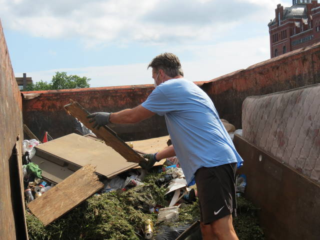<p>Wilkes-Barre City Councilman Tony Brooks tosses debris into a dumpster outside the station.</p>