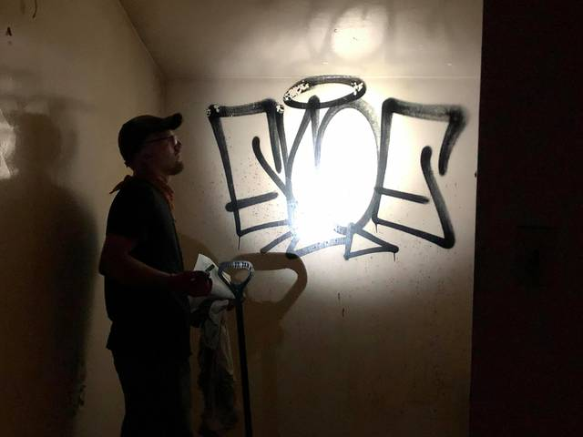<p>Volunteer Damian Bullock examines graffiti in a second-floor room of the station.</p>
