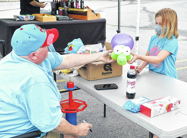 <p>Balloon artist TJ Belt of Jubilee Balloons hands 8-year-old Lexi Bartel a balloon animal while attending the Pittston's Farmers Market.</p> <p>Tony Callaio | For Sunday Dispatch</p>