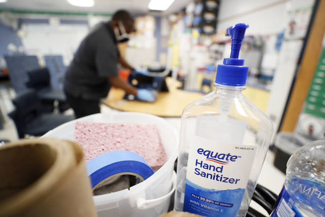 <p>A bottle of hand sanitizer sits on a cart as Des Moines Public Schools custodian Tracy Harris cleans a chair in a classroom at Brubaker Elementary School in Des Moines, Iowa.</p>