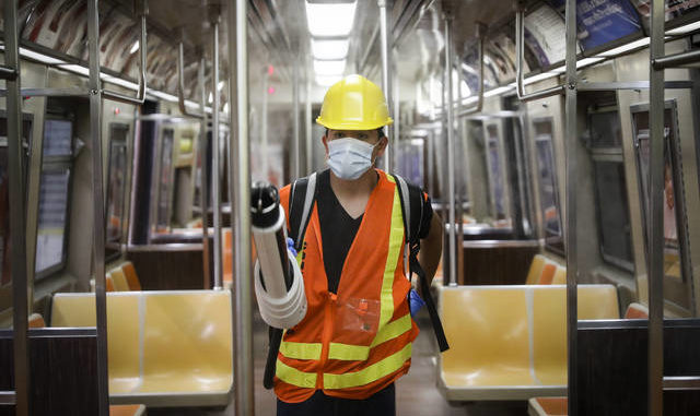 A contractor uses an electrostatic sprayer to disinfect subway cars at the 96th Street station to control the spread of COVID-19 on Thursday in New York. Mass transit systems around the world have taken unprecedented — and expensive — steps to curb the spread of the coronavirus, including shutting down New York subways overnight and testing powerful ultraviolet lamps to disinfect seats, poles and floors. John Minchillo | AP photo