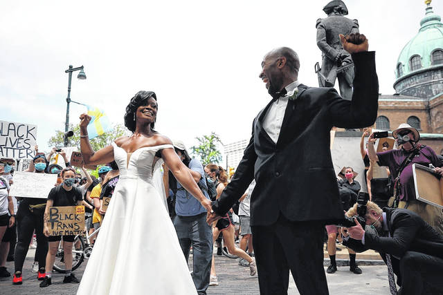 <p>In this June 6, 2020, file photo, Kerry Anne Perkins and Michael Gordon came out to the crowd during a protest in Philadelphia over the death of George Floyd. The couple realized amid the pandemic they would have to cancel their wedding but wound up having a microwedding. As they did their first look, a massive Black Lives Matter demonstration arrived at Philadelphia's Logan Square. Photos of the couple holding hands, fists raised, with thousands of people surrounding them went viral.</p> <p>AP photo</p>