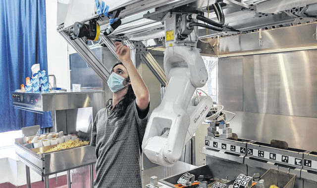 A technician makes an adjustment to a robot at Miso Robotics' White Castle test kitchen in Pasadena, Calif. Robots that can flip burgers, make salads and even bake bread are in growing demand as virus-wary kitchens try to put some distance between workers and customers. Starting this fall, the White Castle burger chain will test the robot arm that can cook french fries and other foods. The robot, dubbed Flippy, is made by Pasadena, California-based Miso Robotics.
