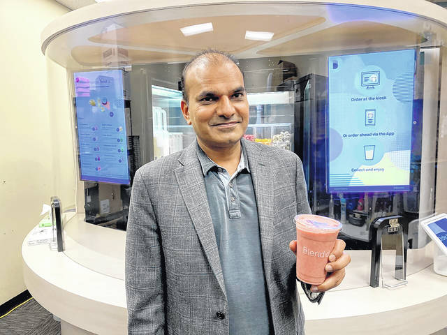 <p>Vipin Jain, CEO and cofounder of Blendid, holds a smoothie in Sunnyvale, Calif., made by his company's robotic kiosk that makes blended fruit drinks with no human intervention.</p>