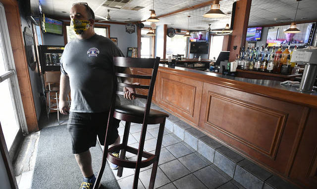 BigDogz Grill owner Michael Ziants removes the last chair from his bar in Johnstown to comply with Governor's Wolf new COVID-19 restrictions for bars on Thursday. Todd Berkey | The Tribune-Democrat via AP