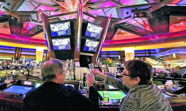 Gene Schulp, left, and Lori Scalzo, both of West Pittston, toast with their glasses of champagne after a countdown to noon on New Year's Eve 2016 at the casino bar at Mohegan Sun Pocono in Plains Township. Mohegan Sun Pocono says it will stop serving alcoholic beverages on the gaming floor in the wake of new guidance issued by the state regarding Gov. Tom Wolf's latest order to businesses.