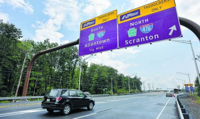 A vehicle drives under signs on the Northeast Extension of the Pennsylvania Turnpike in Penn Forest Township in Carbon County. Turnpike officials have announced yet another toll increase — 6% beginning early next year — as well as a new 45% surcharge for non-EZ-Pass users whose tolls are assessed by mail based on their license plates. Times Leader file photo