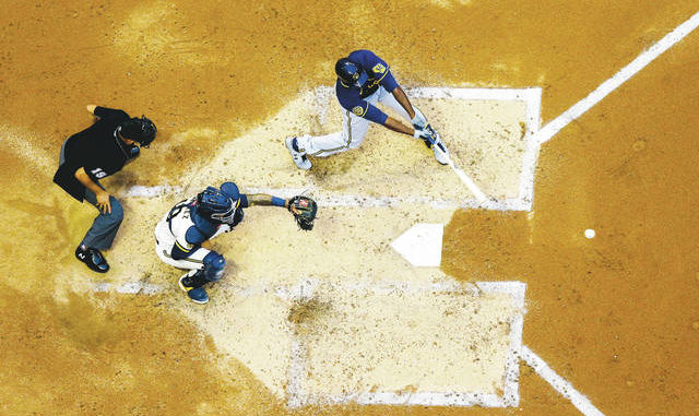 As baseball attempts to play a shortened 60-game regular season amid a coronavirus pandemic, there is some concern that home plate could become a hot spot for transmission. Morry Gash | AP file photo