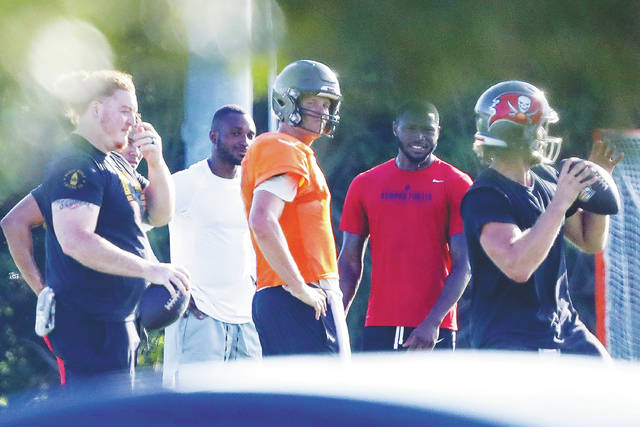 <p>New Buccaneers quarterback Tom Brady, center in orange, organized informal workouts with teammates depsite union recommendations against it during the pandemic.</p> <p>Chris Urso | AP file photo, Tampa Bay Times</p>