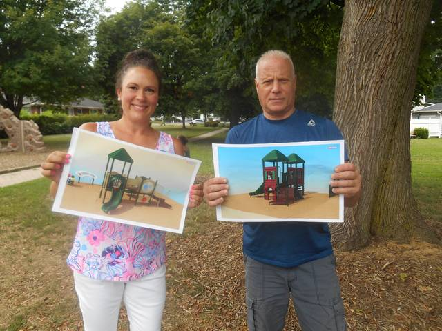 <p>Forty Fort Councilwoman Kristy Dadurka and playground commitee volunteer Jerry Lamark show pictures of playground equipment they would like to see added to the Betty Mascelli Park in Forty Fort.</p> <p>Mary Therese Biebel | Times Leader</p>