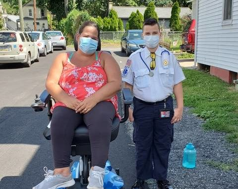 Ann-Marie Kelly is shown in her new Jazzy Air 2 Power Wheelchair next to her neighbor, Junior Fire Chief Brian Lyons, on their street in Plymouth. Submitted photo