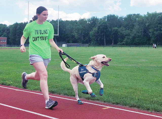 <p>Megan Hale, who is visually impaired, runs on the high school track near her home in West Sand Lake, N.Y., with her guide dog Hero. Hero is from Guiding Eyes for the Blind, which developed a program to train dogs to guide blind runners during workouts in addition to daily activities.</p> <p>AP photo</p>