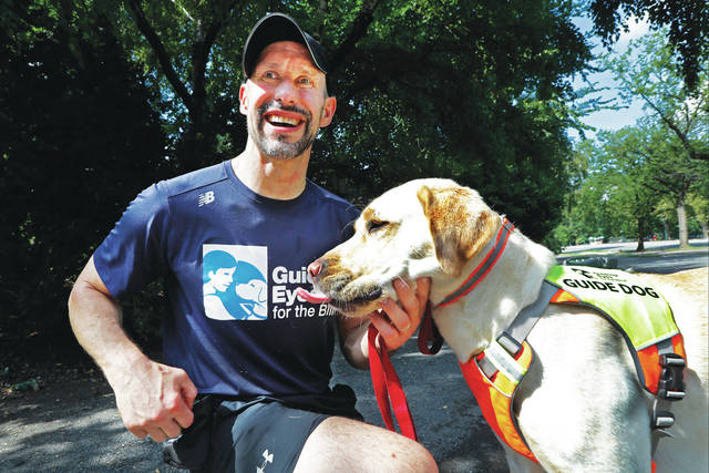 <p>Thomas Panek pauses with his Labrador retriever, Blaze, a trained guide dog, after running in Central Park in New York.</p> <p>AP photo</p>
