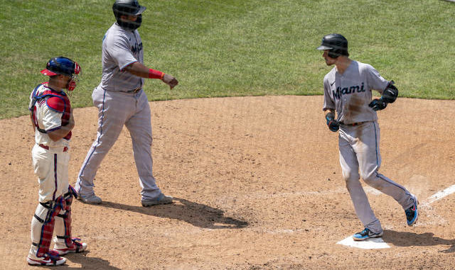 The Miami Marlins' Brian Anderson, right, comes in to score on his two-run home run with Jesus Aguilar, center, as Philadelphia Phillies catcher J.T. Realmuto, left, looks on during the fifth inning of a game Sunday in Philadelphia. AP photo