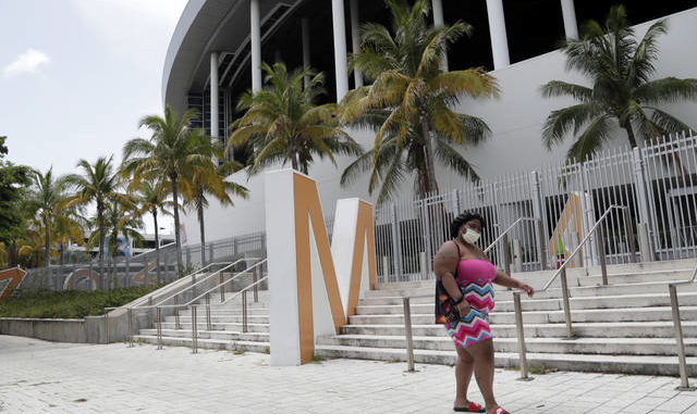A woman wearing a protective face covering walks past Marlins Park 0n Monday in Miami. The Marlins home opener against the Baltimore Orioles on Monday night has been postponed as the Marlins deal with a coronavirus outbreak that stranded them in Philadelphia. AP photo
