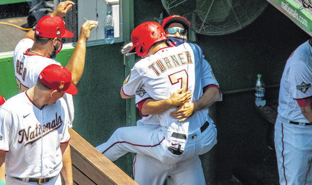 The Washington Nationals' Trea Turner jumps into the arms of a teammate after his solo home run during the third inning of a game against the New York Yankees at Nationals Park on Sunday in Washington.