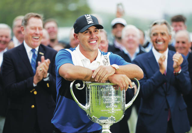 <p>In this May 19, 2019, file photo, Brooks Koepka poses with the Wanamaker Trophy after winning the PGA Championship golf tournament at Bethpage Black in Farmingdale, N.Y. Koepka will try to become the first player to win the PGA Championship three straight times in stroke play starting Aug. 6, 2020, and there will not be anyone at Harding Park to cheer him on.</p>