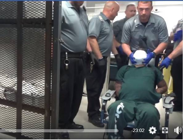 <p>This screen capture from a video released to social media on Wednesday shows Shaheen Mackey in a restraint chair surrounded by corrections officers at the Luzerne County Correctional Facility in June 2018.</p>
