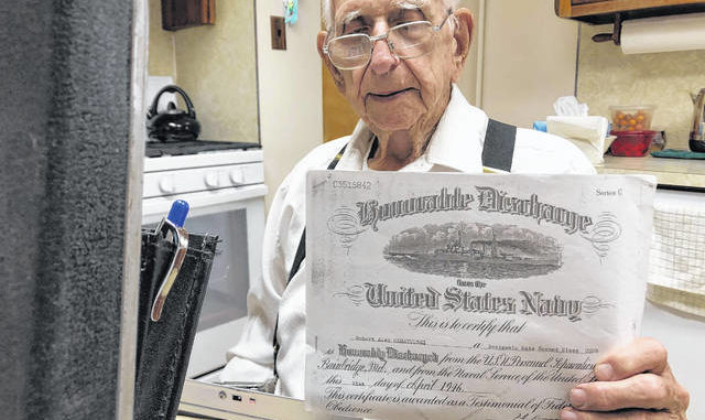 Forty Fort resident Bob Megatulski, 95, who served in the Pacific Theater with the U.S. Navy Seabees during World War II, holds up a copy of his 1946 discharge papers last week during an interview at his home. Roger DuPuis | Times Leader