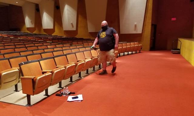 A worker uses an electrostatic sprayer to disinfect auditorium seats after a Greater Nanticoke Area School Board meeting Thursday. The board opted to meet in person with board members distanced on the stage, audience members distanced in the seats with aisles taped off limits, and everyone wearing masks. Mark Guydish | Times Leader