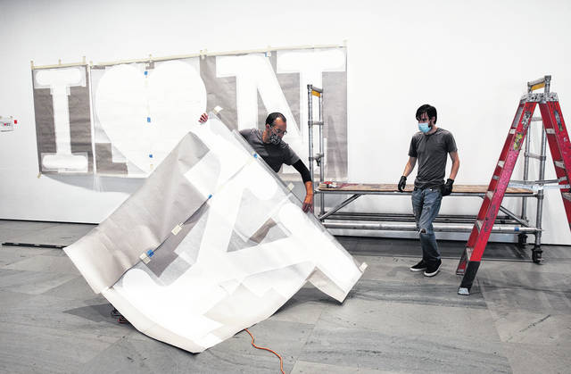 George Vealsquez, left, and Charles Lester install templates for 'I Love NY' at the entrance to the Museum of Modern Art in New York. The work by graphic designer Milton Glaser will be done in red for the heart and black for the lettering. MOMA reopened Thursday.                                  AP photo