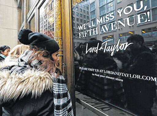 In this Jan. 2, 2019 file photo, women peer in the front door of Lord & Taylor's flagship Fifth Avenue store which closed for good, in New York. A slew of once-beloved brands from Lord & Taylor to Ann Taylor have filed for Chapter 11 since the pandemic. Many shoppers will see these iconic labels vanish or become mere shadows of themselves as they drastically shrink their businesses or get acquired. But while loyal customers bemoan their loss, the brands themselves have been clearly losing favor for year.                                  AP photo