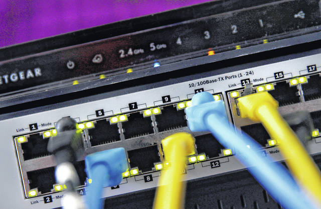 """In this June 19, 2018, file photo a router and internet switch are displayed in East Derry, N.H. Not all that long ago, managing your home network's security didn't involve much more than installing an antivirus program on your PC. If only it were still so simple. Home networks are a major target for cybercriminals, who use innocuous smart gadgets as stepping stones to loot data from PCs and phones. Or they may co-opt the simpler devices into much larger """"botnets"""" that can be used to wreak havoc across the internet.                                  AP photo"""
