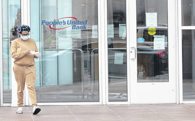 A woman wearing a face mask to protect against the coronavirus takes off disposable gloves after using an ATM at the People's United Bank on Main Street in downtown in Bridgeport, Conn. As bank branches remain shuttered, more people are having a go at doing their banking online.                                  AP photo