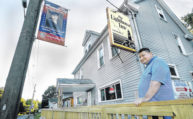The owner of the Lighthouse Inn, Michael Holcomb, stands in front of his establishment in West Wyoming. The Hometown Hero pennant hanging on a utility pole in front of his bar honors his father, Harold Herbert Holcomb.                                  Fred Adams | For Times Leader