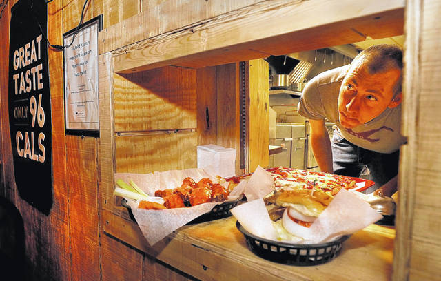 <p>The cook at the Lighthouse Inn in West Wyoming peers out of a window after placing a food order for pick up recently.</p>                                  <p>Fred Adams | For Times Leader</p>