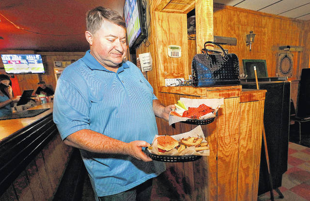 <p>Michael Holcomb carries a food order to the dinning room in the back of The Lighthouse in West Wyoming.</p>                                  <p>Fred Adams | For Times Leader</p>