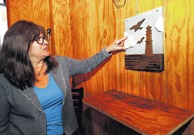 <p>Jill Holcomb, wife of Michael Holcomb, shows off a wooden relief piece of art a patron made for the bar that resembles the logo on the sign in front of The Lighthouse Inn in West Wyoming.</p>                                  <p>Fred Adams | For Times Leader</p>