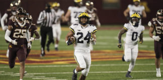 Michigan running back Zach Charbonnet (24) carries for a touchdown against Minnesota in the first half of an NCAA football game Saturday in Minneapolis.                                  AP photo