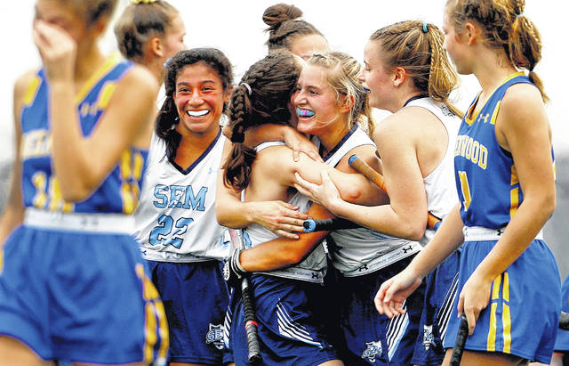 Wyoming Seminary's Anna Mozeleski (center) is huged by Maddie Olshemski as Ella Babacci is all smiles to the left after Anna Moleskeski scored the third goal in the PIAA Class A FIeld Hockey State Championship Game on Saturday in White Hall. Seminary defeated Greenwood 3-0 to win the title.                                  Fred Adams | For Times Leader