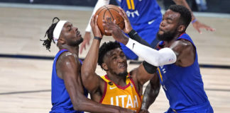 In this Aug. 30, 2020, file photo, Utah Jazz's Donovan Mitchell, center, goes up to shoot as Denver Nuggets' Jerami Grant, left, and Paul Millsap, right, defend during the second half of an NBA first round playoff game in Lake Buena Vista, Fla. Mitchell agreed Sunday to a five-year, $163 million extension to remain with the Jazz.